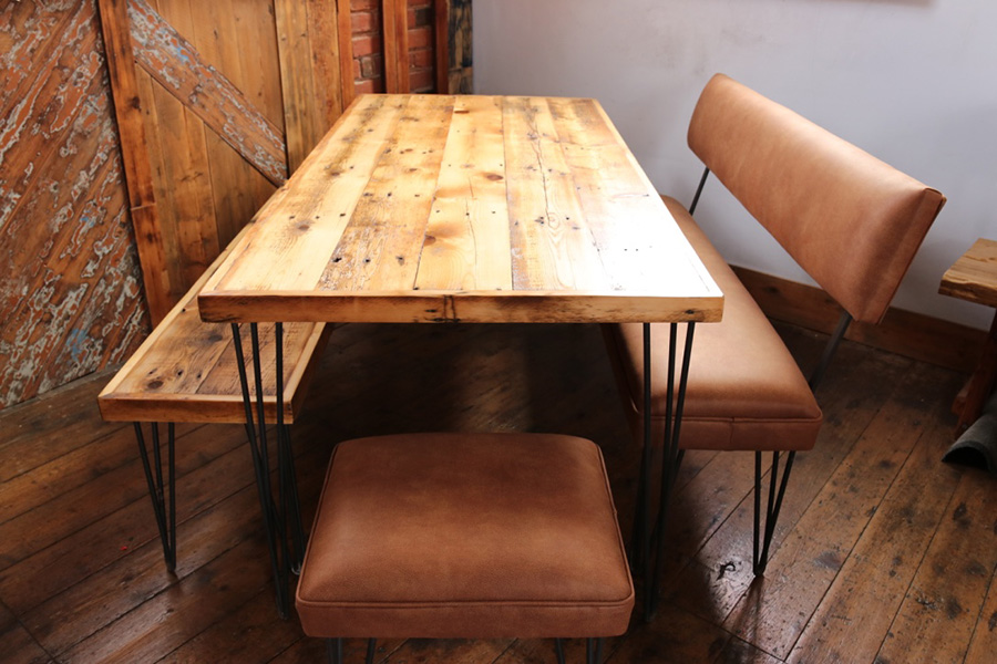 reclaimed wooden dining table with leather bench and industrial bench